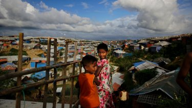 Rohingya children overlook an expanse of makeshift bamboo and tarp shelters at Kutupalong refugee camp.