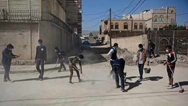 Yemeni youths clean a street during a national cleanup campaign in Sanaa, Yemen, last week.