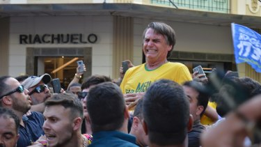 Then presidential candidate Jair Bolsonaro grimaces right after being stabbed in the stomach during a campaign rally in Juiz de Fora, Brazil, in 2018.