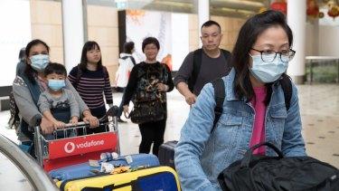 Passengers arrive at Sydney Airport wearing masks.