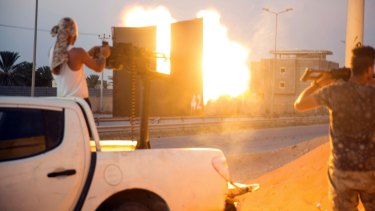 A fighter under the UN backed government shooting with an anti-aircraft gun  during the clashes in Wadi Alrabie south of Tripoli, on Friday.