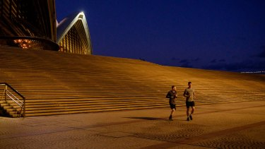 Sydney Opera House is deserted except for distanced joggers.