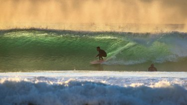 Surfers use the growing swell along the Sydney coast.