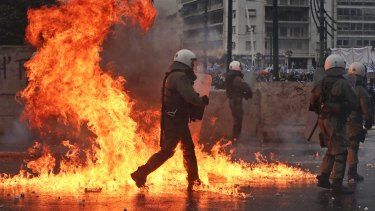 A molotov cocktail explodes next to Greek riot police during clashes after a rally in Athens on Sunday.
