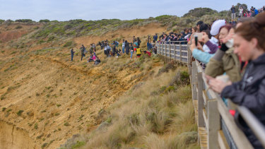 Tourists pose for photos outside the designated viewing area for the Twelve Apostles at Port Campbell.