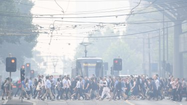 Commuters in Melbourne confront severe smoke haze on Tuesday.