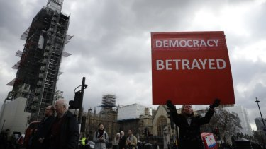 A pro-Brexit supporter holds up a placard outside the Houses of Parliament.