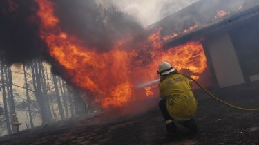 Firefighters work to save a property in the NSW Southern Highlands on Thursday.