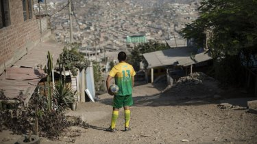 A football player looks over Pamplona shanty town in Lima, Peru, on March 13.