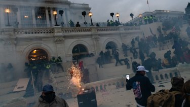 A flashbang grenade explodes as law enforcement officers push back demonstrators at the US Capitol building.