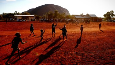 Children playing footy during the closing ceremony of a Mutitjulu community in Uluru.