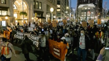 Demonstrators march down Fifth Avenue towards Washington Square Park in New York.