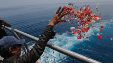 A relative sprinkles flowers for the victims of the crashed Lion Air flight 610 from an Indonesia Navy ship in the waters where the plane is believed to have crashed.
