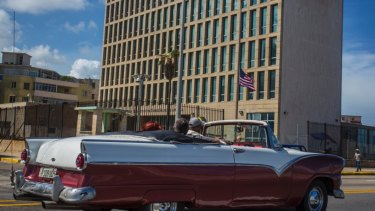 A classic convertible drives past the United States embassy in Havana, Cuba.