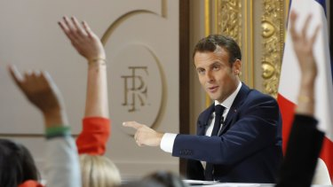 Reporters raise their hands at French President Emmanuel Macron's news conference at the Elysee Palace on Thursday.