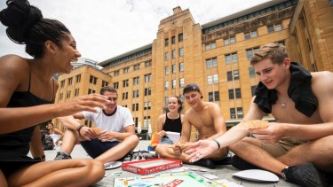 German backpackers get involved in a game of Monopoly in front of the MCA as they wait for the fireworks.
