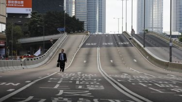 A man walks alone on a empty road near the Legislative Council after protesters continue to protest against the extradition bill in Hong Kong.