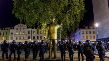 Police stand around the statue facing the crowd, before the controversial artwork was removed.
