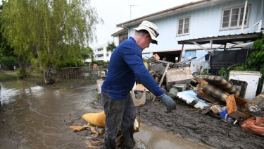 Chris Mitchell removes flood damaged items out of his father in-law's house in the suburb of Rosslea in  flood-affected Townsville