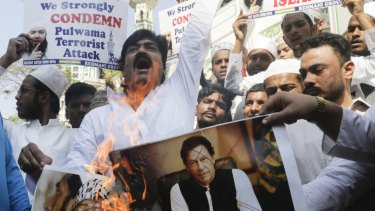 Indian muslims burn posters of Pakistani prime minister Imran Khan, center, and Hafiz Saeed, chief of Pakistani religious group Jamaat-ud-Dawa, during a protest against Thursday's attack on a paramilitary convoy in Kashmir.