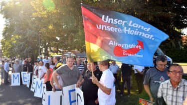 """AfD supporters hold posters """"Merkel must go"""" and a flag """"Our country, our homeland """" last year."""