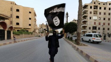 A member of Islamic State waves an IS flag in Raqqa, Syria.