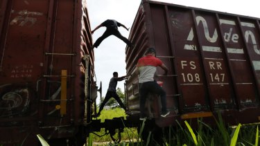 Migrants catch a ride on a freight train on their way north to the US, in Salto del Agua, Chiapas state, Mexico, on Tuesday.