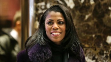 Omarosa Manigault smiles at reporters as she walks through the lobby of Trump Tower in New York.