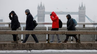 Hard to imagine a water shortage: Commuters make their way across London Bridge facing inclement weather in London, UK.