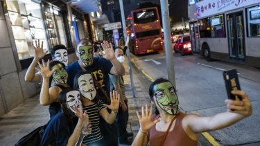 Demonstrators wearing face masks pose for a selfie during the Face Mask Way event in Hong Kong.