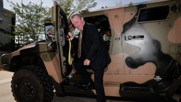 Then minister for defence industry Christopher Pyne steps out of a Hawkei vehicle in January.