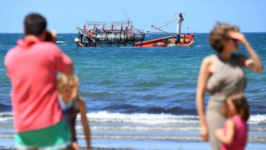 A sunken fishing vessel, believed to be carrying Vietnamese asylum seekers, is seen off the beach at Cape Kimberley at the mouth of the Daintree River.
