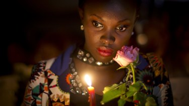 A Kenyan holds a candle and flowers as she listens to the names of each of the victims of the Garissa attack being read out aloud, during a vigil at Uhuru Park in Nairobi,in 2015.