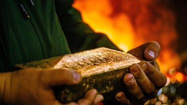 A worker carries a 28 kilogram gold bar after casting and cleaning in the foundry at the South Deep gold mine in South Africa.