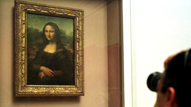 The Mona Lisa behind protective glass in the Louvre.