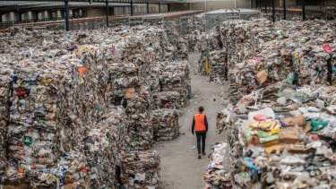 A warehouse stacked to the rafters with bales of waste intended for recycling.