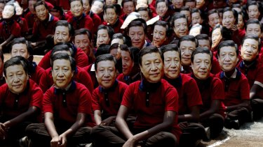Indian school children wear face masks of Chinese President Xi Jinping to welcome him on the eve of his visit in Chennai, India.
