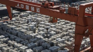 A gantry crane stands as bundles of aluminum ingots sit stacked at a stockyard in Wuxi, China.