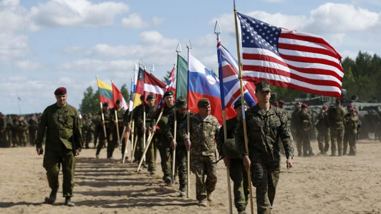 """A Slovenian, third in line, joins fellow soldiers from NATO countries - including US, UK, and Canada, at  the opening ceremony of military exercise """"Sabre Strike 2015""""."""