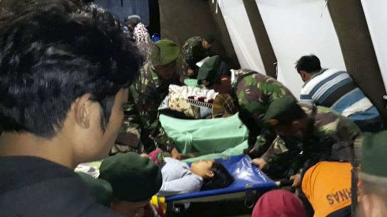 Indonesian soldiers tend to a woman injured in the earthquake at a makeshift hospital in Lombok.