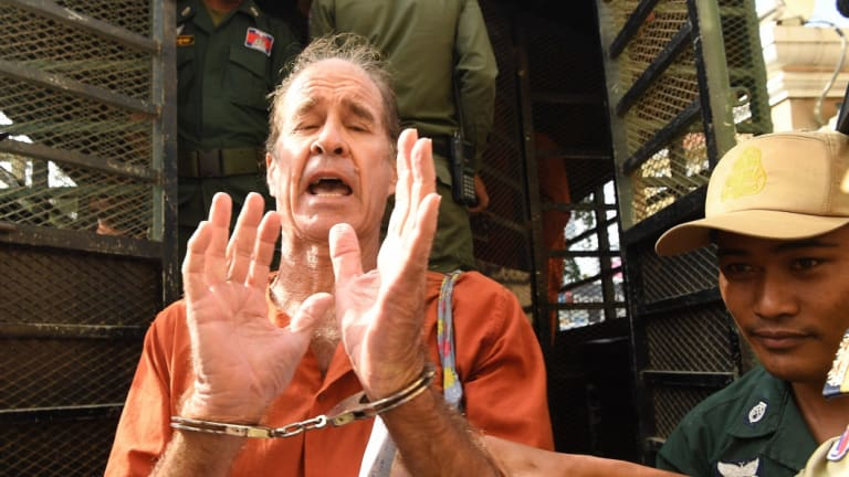 James Ricketson who is accused of espionage leaves the prison van as he arrives at the Phnom Penh Municipal Court for a court appearance in June.