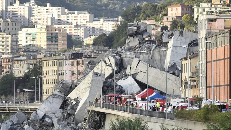 Rescuers work to recover an injured person after the Morandi highway bridge collapsed in Genoa, northern Italy, on Tuesday.