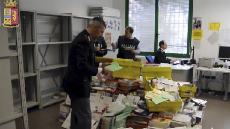 Italian postal police officers sort undelivered mail found in a postman's garage, in Vicenza, northern Italy, before the 2010 elections.