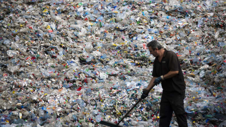 A worker sweeps crushed plastic bottles and containers ahead of sorting in the Netherlands.