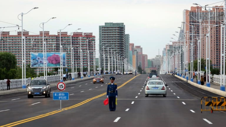 A police man directs traffic on a street lined with apartment buildings in Pyongyang.