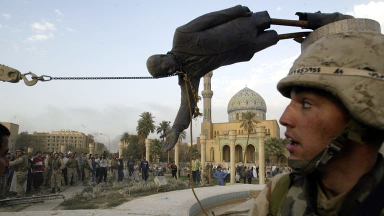 Iraqi civilians and US soldiers pull down a statue of Saddam Hussein in downtown Baghdad, in April 2003.