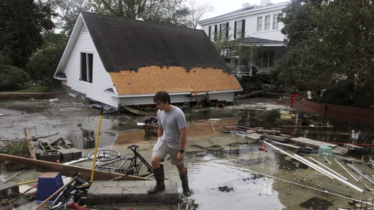 Resident Joseph Eudi looks at flood debris and storm damage from hurricane Florence at a home on East Front Street in New Bern, North Carolina on Saturday.