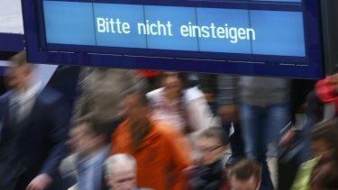 People walk under the sign reading 'Please do not board' at the main train station in Frankfurt, Germany.