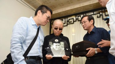 Liu Xia, centre, holds her husband's portrait during his funeral in Shenyang in July 2017.