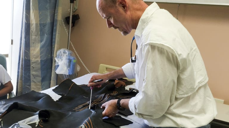 Chris Lowe, director of the Shark Lab at California State University, Long Beach, analyses the mangled wetsuit Maria Korcsmaros was wearing when she was attacked.